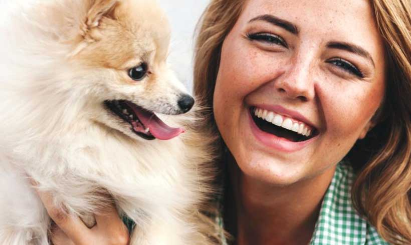 Image of a dog and smiling pet owner